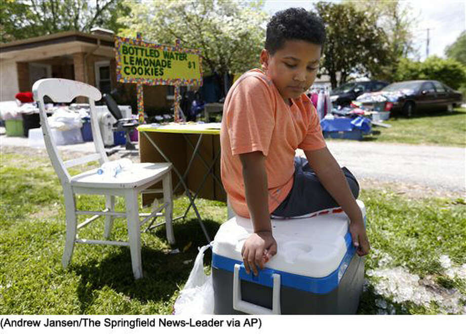 In this April 22, 2016 photo, Tristan Jacobson sits on a water cooler in front of his lemonade stand outside his home in Springfield, Mo. Tristan has been living with with Donnie and Jimmy Davis, who have been Tristan's kinship guardians. They have been holding a yard sale and set up a lemonade stand to raise money for his adoption. (Andrew Jansen/The Springfield News-Leader via AP) NO SALES; MANDATORY CREDIT Photo: Andrew Jansen
