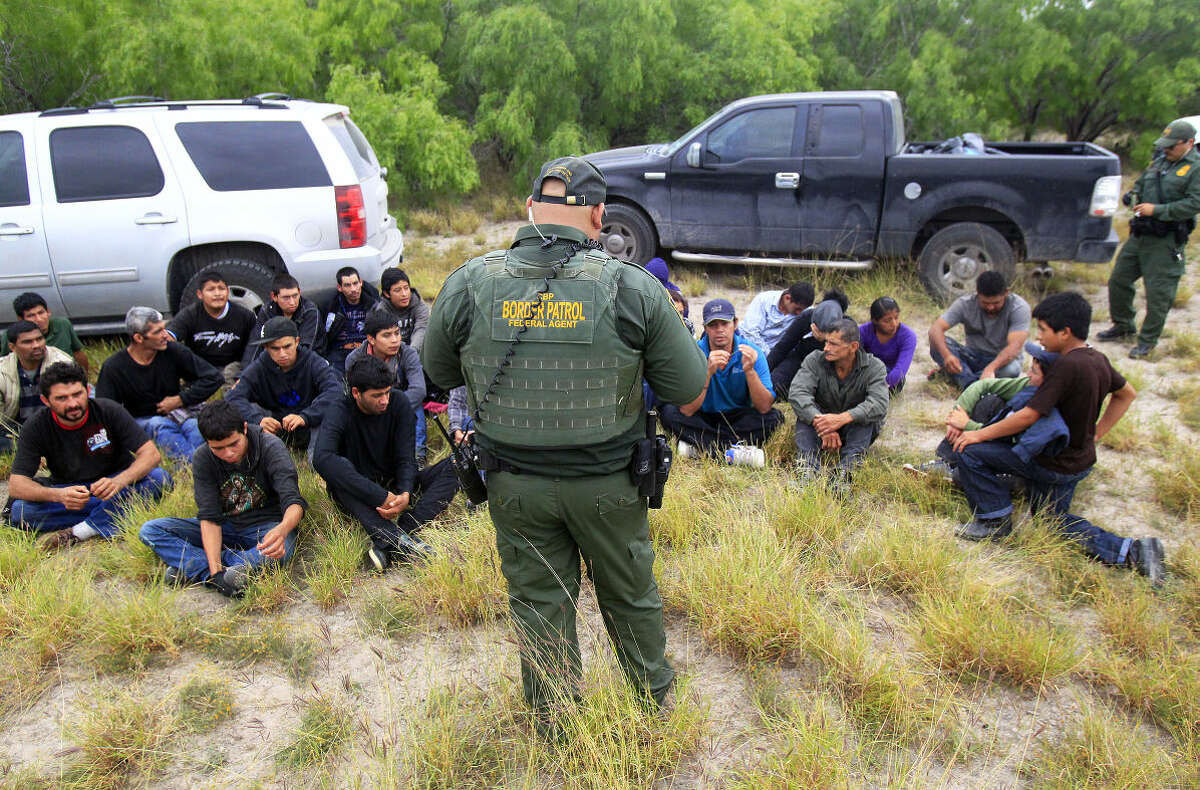 In this Thursday, April 17, 2014 photo, immigrants suspected of being in the country illegally sit in a group after U.S. Border Patrol agents detained at least 80 immigrants who'd been living in a makeshift encampment in suburban McAllen, Texas.