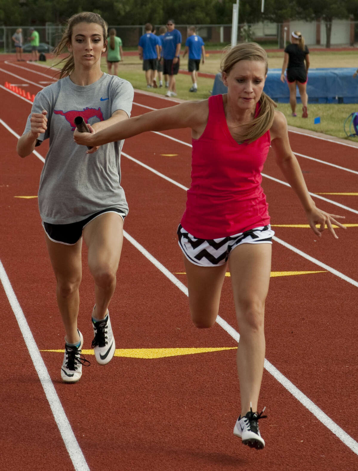 Midland Christian's Kenzie Pullen hands off to Rylee Hill Wednesday, 5-6-15, as they and others prepare for the state championship meet. Tim Fischer\Reporter-Telegram