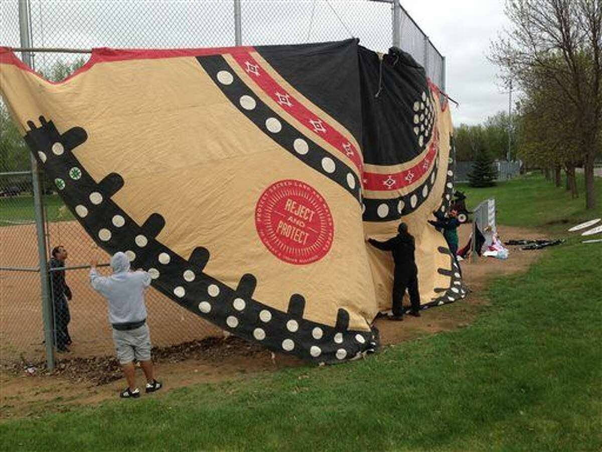 Opponents of the construction of the proposed Keystone XL pipeline, which would cut through South Dakota, erect a teepee across from the arena where President Barack Obama is planned to address graduates of the Lake Area Technical Institute later Friday, May 8, 2015 in Watertown, S.D. during the school's commencement ceremony. (AP Photo/Regina Garcia Cano)