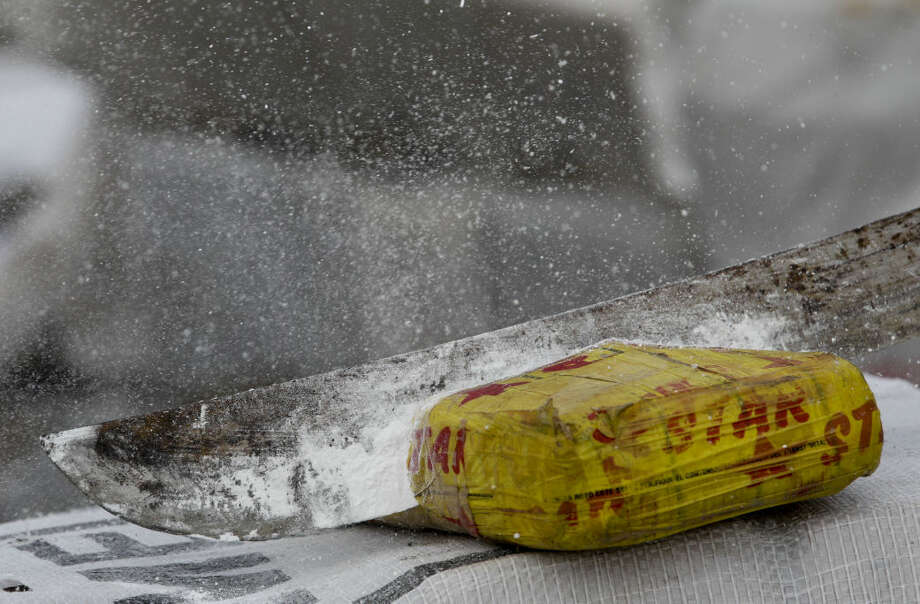 Powder flies as an anti-narcotics agent hacks open a package of cocaine with a machete before it's burned on the outskirts of Panama City, Friday, Dec. 5, 2014.  Photo: Arnulfo Franco