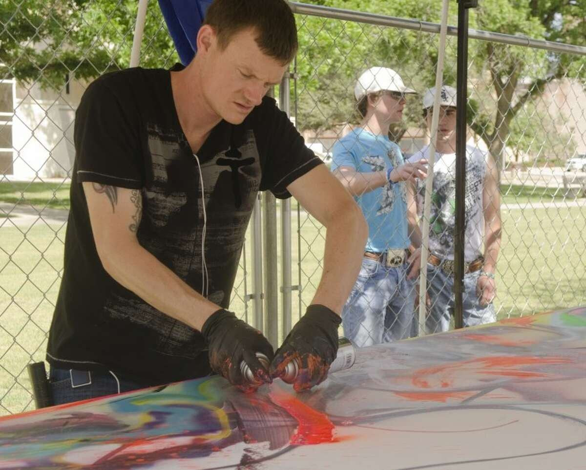 Brad King, a spray paint artist, works on a piece, Youth, at Celebration of the Arts 2012.