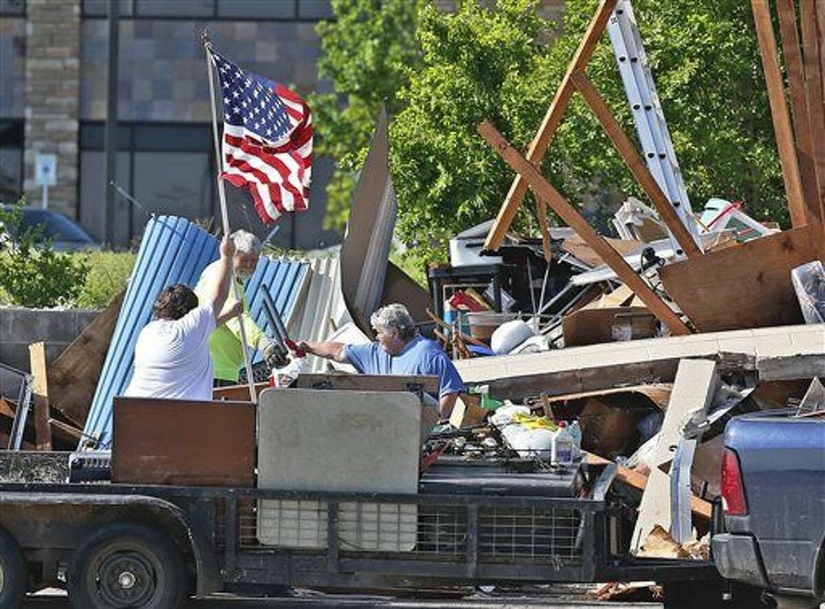 Jim Bresee, center, smiles as his daughter, Sandra Silvy, left, raises a flag in what is left of the Bresee's storage unit following Wednesday's storm in Oklahoma City, Thursday, May 7, 2015. His wife Carol Bresee is at right. The three are attempting to salvage what they can from the unit, but much is damaged due to rain. Gov. Mary Fallin has declared a state of emergency in 12 Oklahoma counties hit by tornadoes, severe storms, straight-line winds and flooding. (AP Photo/Sue Ogrocki)