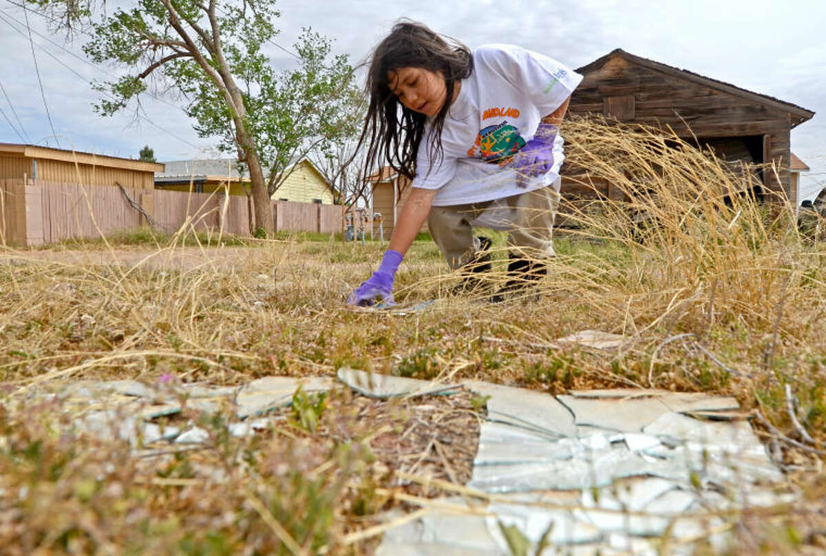 Krizzandra Gomez, age 7 cleans up trash with her family in a lot located near E. Golf Course Rd. and N. Lamesa. The Great American Cleanup//Don't Mess with Texas Trash-Off was co-sponsored by the Texas Department of Transportation, Keep America Beautiful, and Keep Texas Beautiful. James Durbin/Reporter-Telegram