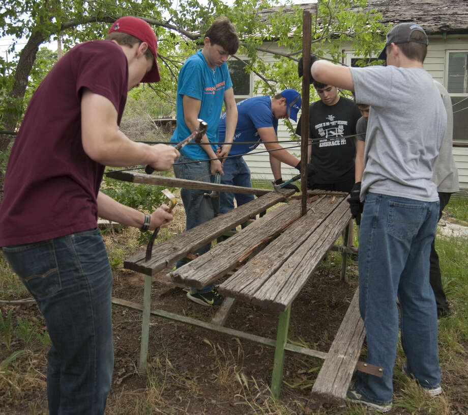 Midland Christian 10th graders tear down an old picnic table as part of the work on a Christmas in Action house project Wednesday, 4-22-15, as part of the schools Day of Service. Tim Fischer\Reporter-Telegram Photo: Tim Fischer