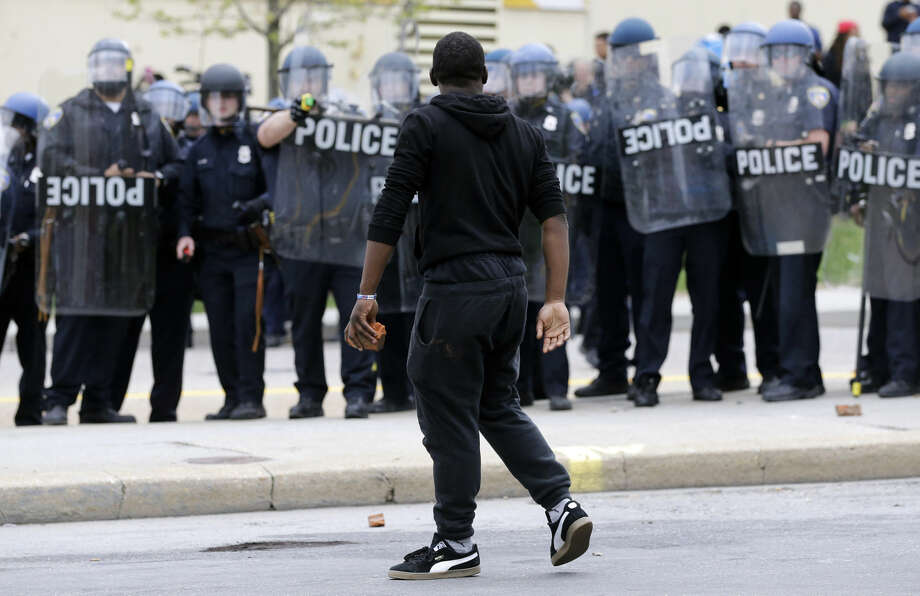 A demonstrator walks past police with a brick as they respond to thrown objects, Monday, April 27, 2015, after the funeral of Freddie Gray in Baltimore. Gray died from spinal injuries about a week after he was arrested and transported in a Baltimore Police Department van. (AP Photo/Patrick Semansky) Photo: Patrick Semansky
