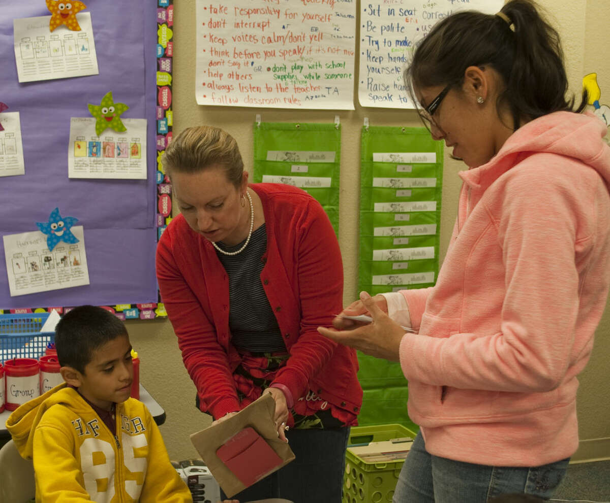 Jessica Scheig second grade teacher at Midland Academy helps Daniel Hidrogo read the clues to his mom, Patty Hidrog, so she can guess what is in the bag Thursday at Midland Academy Family Fun Night. Tim Fischer\Reporter-Telegram