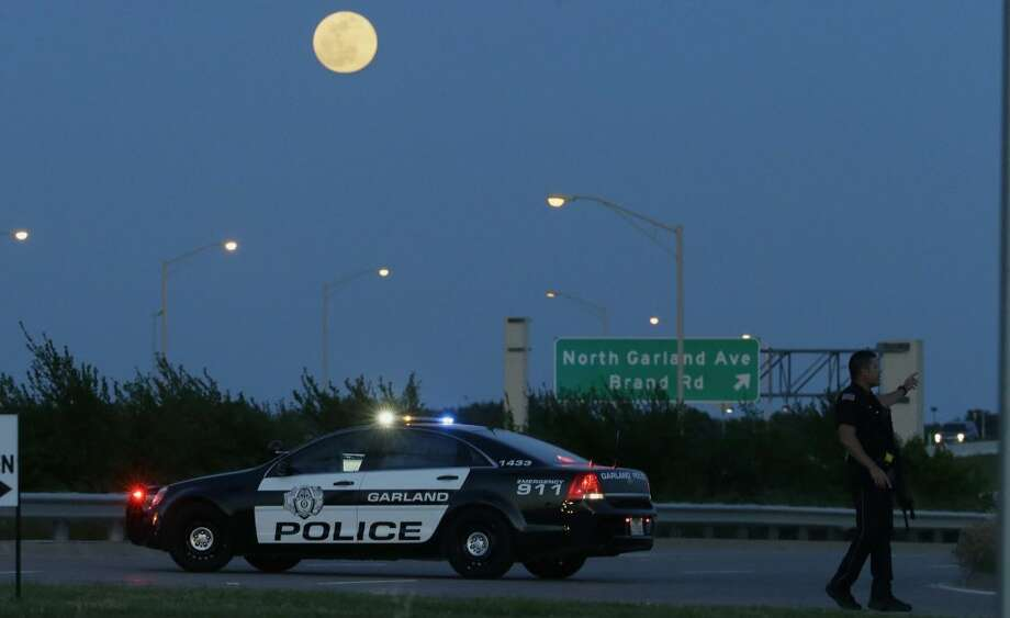 An armed police officer stands guard on a road near the Curtis Culwell Center where a provocative contest for cartoon depictions of the Prophet Muhammad was held Sunday, May 3, 2015, in Garland, Texas. The contest was put on lockdown Sunday night and attendees were being evacuated after authorities reported a shooting outside the building. (AP Photo/LM Otero) Photo: LM Otero