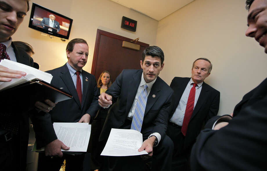 House Budget Committee Chairman Paul Ryan, R-Wis., works with Republican members of the committee on Capitol Hill in Washington, Tuesday, April 5, 2011. He is flanked by Rep. Tom McClintock, R-Calif., right, with Rep. Bill Flores, R-Texas, at left. The pace of budget negotiations in Congress is quickening as a deadline for a government shutdown looms at week's end. (AP Photo/J. Scott Applewhite) Photo: J. Scott Applewhite