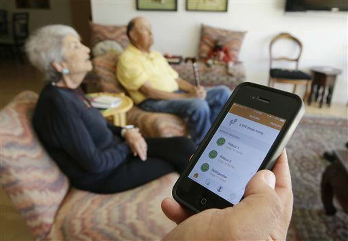 In this March 17, 2015 photo, Phil Dworsky shows off an app on his phone that displays the movements of his parents, Dorothy, 80, left, and Bill Dworsky, 81, rear, at their home in San Francisco. Each time an elder Dworksy opens the refrigerator, closes the bathroom door or lifts the lid on a pill container, tiny sensors in their home make notes on a digital logbook, which the younger Dworsky monitors daily on his smartphone. (AP Photo/Eric Risberg)