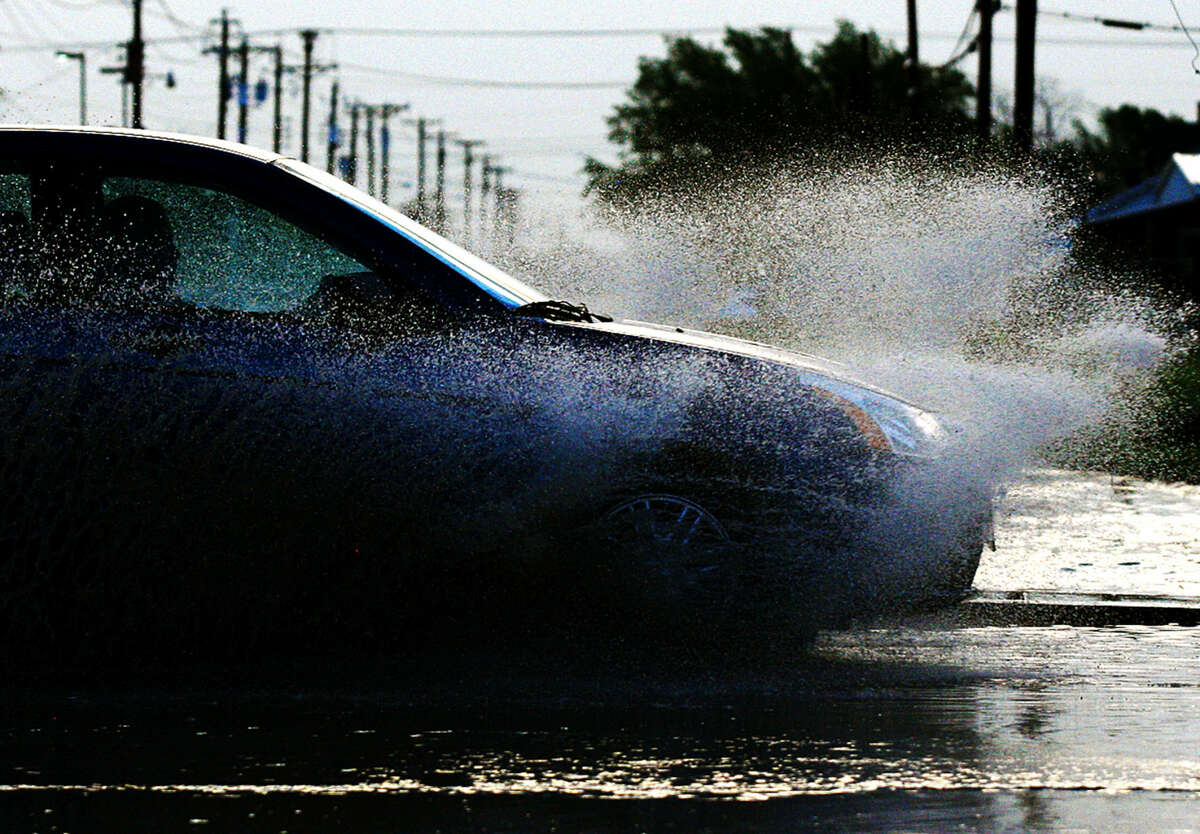 A vehicle splashes through a puddle at the intersection of S. Big Spring St. and W. New York Ave. after a thunderstorm passed through Midland County on Wednesday, April 8, 2015. James Durbin/Reporter-Telegram