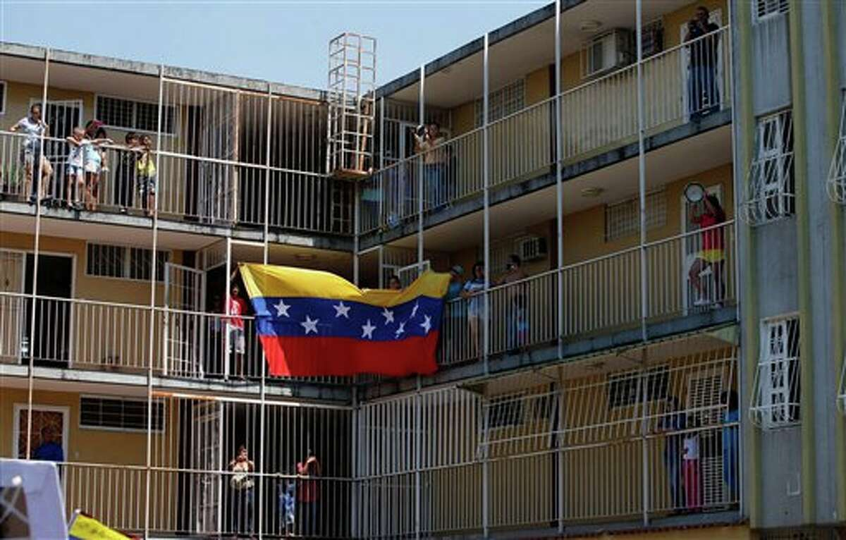 People hold a Venezuelan national flag as demonstrators march through the streets of the Isabelica neighborhood protesting the deaths of two residents, killed by unknown gunmen earlier in the week, in Valencia, Venezuela, Saturday, March 15, 2014. The deaths occurred in the opposition-dominated Isabelica neighborhood, where residents unhappy with the scarcity of basic items and rising unemployment from the closure of some businesses in the area have protested for weeks by blocking streets and throwing rocks at police. (AP Photo/Fernando Llano)
