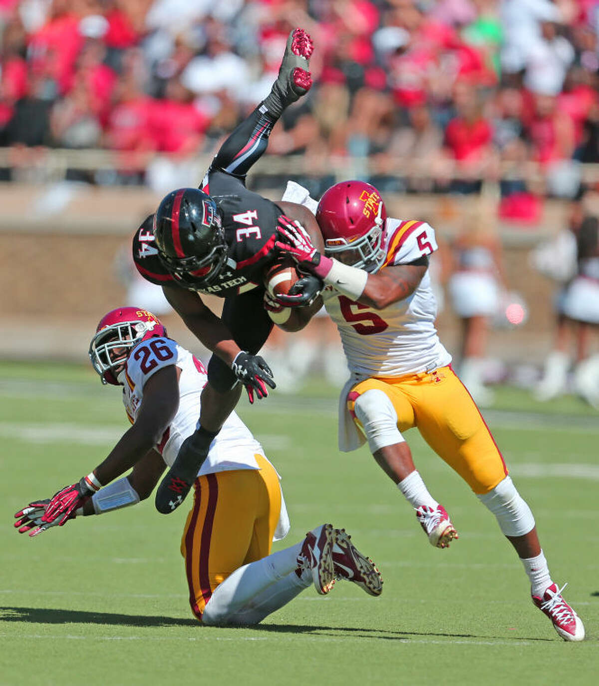Texas Tech running back Kenny Williams (34) hurdles an Iowa State defender prior to being tackled after a large gain in Big 12 action on Oct. 12, 2013 at Lubbock's Jones AT&T Stadium. Wade H. Clay/Special to the MRT
