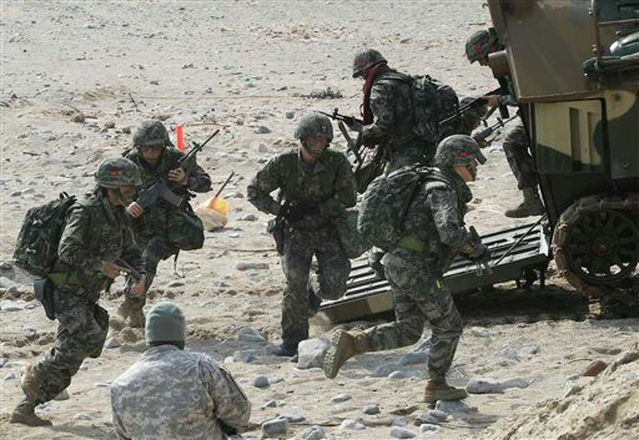 South Korean marines run out from a LVT-7 during the U.S.-South Korea joint landing exercises called Ssangyong, part of the Foal Eagle military exercises, in Pohang, South Korea, Monday, March 31, 2014. South Korea on Monday returned fire into North Korean waters after shells from a North Korean live-fire drill fell south of the rivals' disputed western sea boundary, a South Korean military official said. (AP Photo/Ahn Young-joon) Photo: Ahn Young-joon / AP