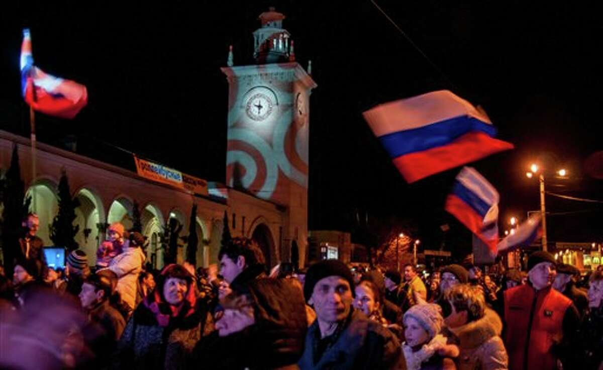 In this photo taken on Saturday, March 29, 2014, Russian flags flutter in the wind near a clock tower at a railway station during celebrations to mark the switch to Moscow time in Simferopol, Crimea. Sevastopol and Crimea switched to Moscow time at 2 a.m. on Sunday, March 30, advancing the clocks by two hours. (AP Photo/Max Vetrov)
