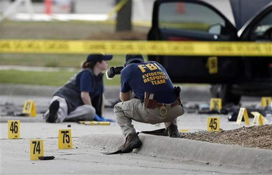 FBI crime scene investigators document the area around two deceased gunmen and their vehicle outside the Curtis Culwell Center in Garland, Texas, Monday, May 4, 2015. Police shot and killed the men after they opened fire on a security officer outside the suburban Dallas venue, which was hosting provocative contest for Prophet Muhammad cartoons Sunday night, authorities said. (AP Photo/Brandon Wade) Photo: Brandon Wade