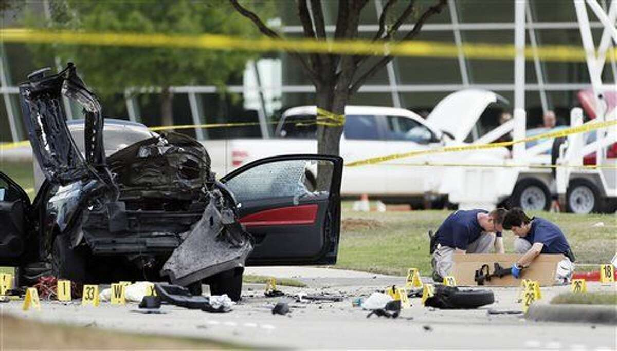 Investigators box up an assault weapon outside the Curtis Culwell Center, Monday, May 4, 2015, in Garland, Texas. Two men opened fire with assault weapons on police Sunday night who were guarding a provocative contest for Prophet Muhammed cartoons. A police officer returned fire killing both men. (AP Photo/Brandon Wade)