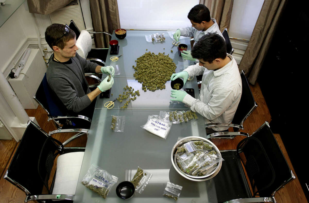 (clockwise from left) Joe, Rigoberto and David package product, at San Francisco's only licensed medical marijuana delivery company