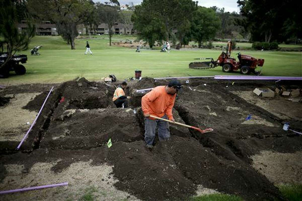 In this April 25, 2015 photo, workers install moisture monitoring and irrigation systems at the El Niguel Country Club in Laguna Niguel, Calif. California's epic drought is reshaping the course at El Niguel Country Club and dozens of others statewide. Pressed by the fourth year of bone-dry weather and the threat of state-mandated water cuts, some of the poshest courses in California are ceding back to nature some of their manicured green, installing high-tech moisture monitoring systems and letting the turf they don't rip up turn just a little bit brown. (AP Photo/Gregory Bull)