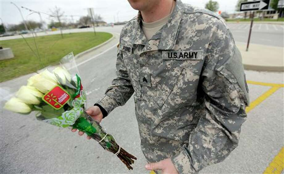 An unidentified soldier holds flowers dropped off at Fort Hood's main gate for shooting victims, Thursday, April 3, 2014, in Fort Hood, Texas. A soldier opened fire Wednesday on fellow service members at the Fort Hood military base, killing three people and wounding 16 before committing suicide. (AP Photo/Eric Gay) Photo: Eric Gay / AP