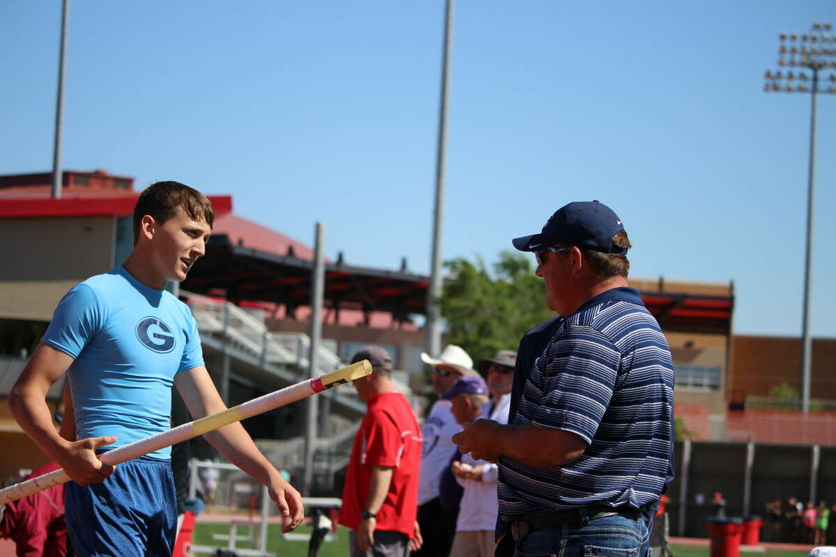 Greenwood's Hunter Wigington talks with pole vault coach Shad Hanna during the Region I-4A Track & Field Championships at Texas Tech on May 1. Photo by James Vint