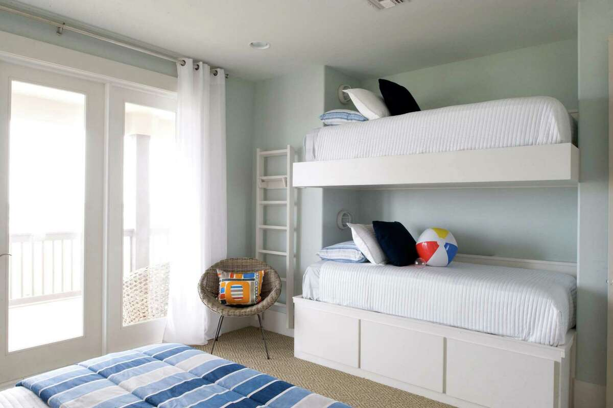 The simplicity of neutrals, with blue and orange accents continues in the bunk bed room in this beach home designed by Courtnay Tartt Elias.