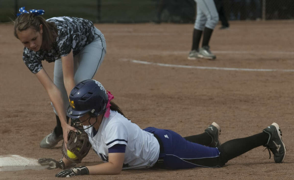 Midland High's Sydney Betcher safely dives back to first as Permian's #32 tries to make the pickoff tag Friday at Audrey Gill Sports Complex. Tim Fischer\Reporter-Telegram