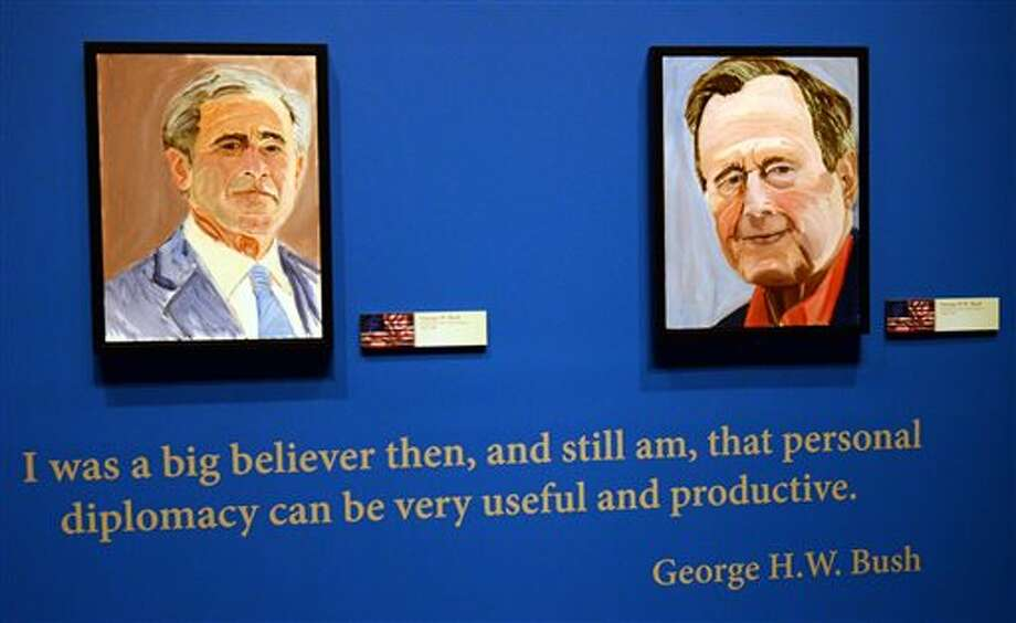 "Portraits of former Presidents Goerge W. Bush, left, and his father George H.W. Bush which are part of the exhibit ""The Art of Leadership: A President's Diplomacy; are on display at the George W. Bush Presidential Library and Museum in Dallas, Friday, April 4, 2014. The exhibit of world leader portraits painted by George W. Bush opens Saturday and runs through June 3. (AP Photo/Benny Snyder)"