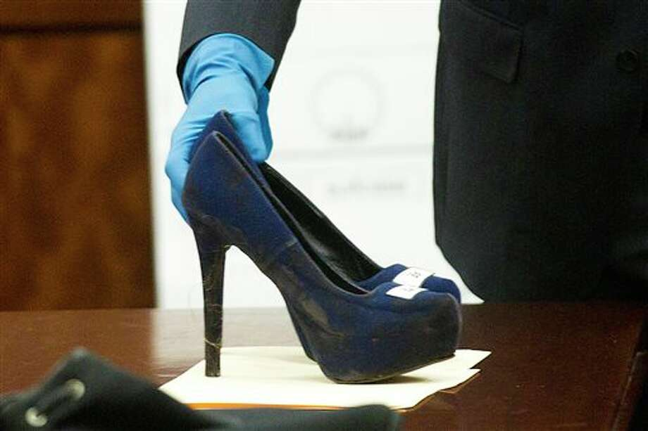 Prosecutor John Jordan sets down a stiletto shoe entered into evidence during the trial against Ana Lilia Trujillo Tuesday, April 1, 2014, in Houston. Trujillo, 45, is charged with murder, accused of killing her 59-year-old boyfriend, Alf Stefan Andersson with the heel of a stiletto shoe, at his Museum District high-rise condominium in June 2013. (AP Photo/Houston Chronicle, Brett Coomer) MANDATORY CREDIT Photo: Brett Coomer / Houston Chronicle