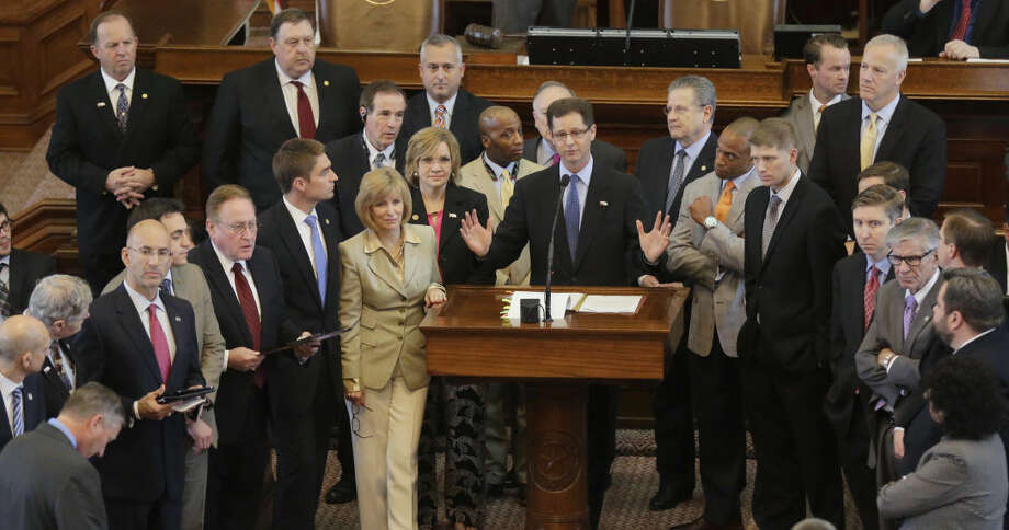 Supporters of a bill letting clergy members refuse to perform same-sex marriages stands with Texas Rep. Scott Sanford, R-McKinney, at podium, in the House Chamber at the Texas Capitol on Thursday in Austin. Photo: Eric Gay/AP