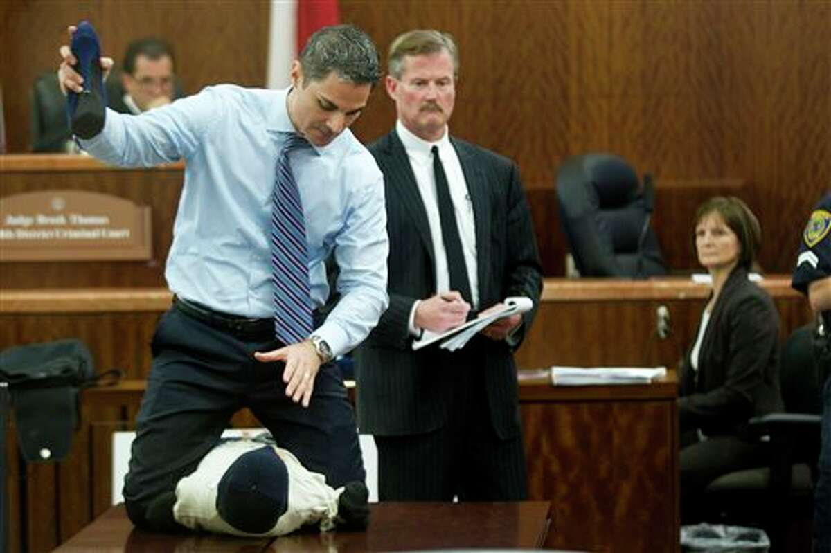 Prosecutor John Jordan does a crime scene demonstration, using a dummy, during the trial against Ana Trujillo Tuesday, April 1, 2014, in Houston. Trujillo, 45, is charged with murder, accused of killing her 59-year-old boyfriend, Alf Stefan Andersson with the heel of a stiletto shoe, at his condominium in June 2013. Defense attorney Jack Carroll, center, and crime scene investigator Christopher Duncan are shown in the background. (AP Photo/Houston Chronicle, Brett Coomer ) MANDATORY CREDIT.