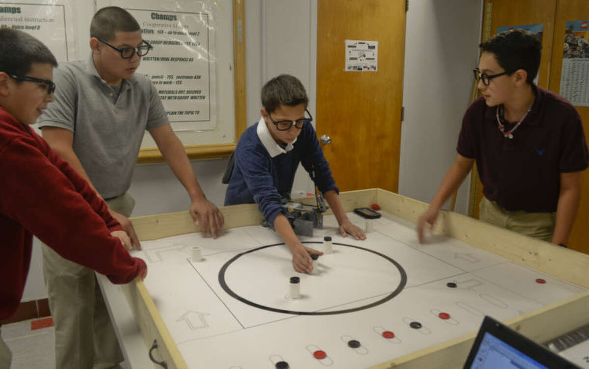 Team Nerd Herd, Christian Pantoja, Sergio Reyes, Cristian Valeriano and Christian Martinez set up the course as they practice with their robot Tuesday at Alamo Junior High. Tim Fischer\Reporter-Telegram