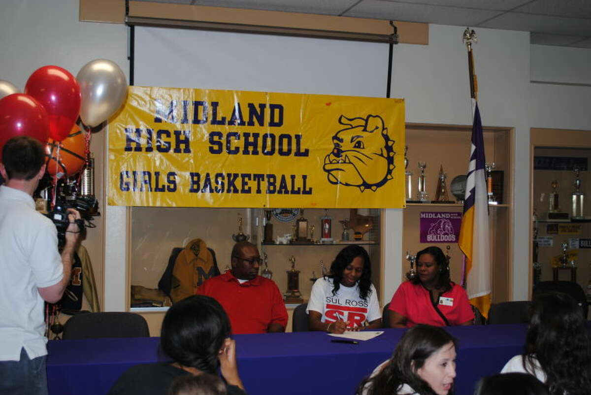 Midland High girls basketball player Desare Allen signs her letter of intent with Sul Ross State University on Wednesday at Midland High.