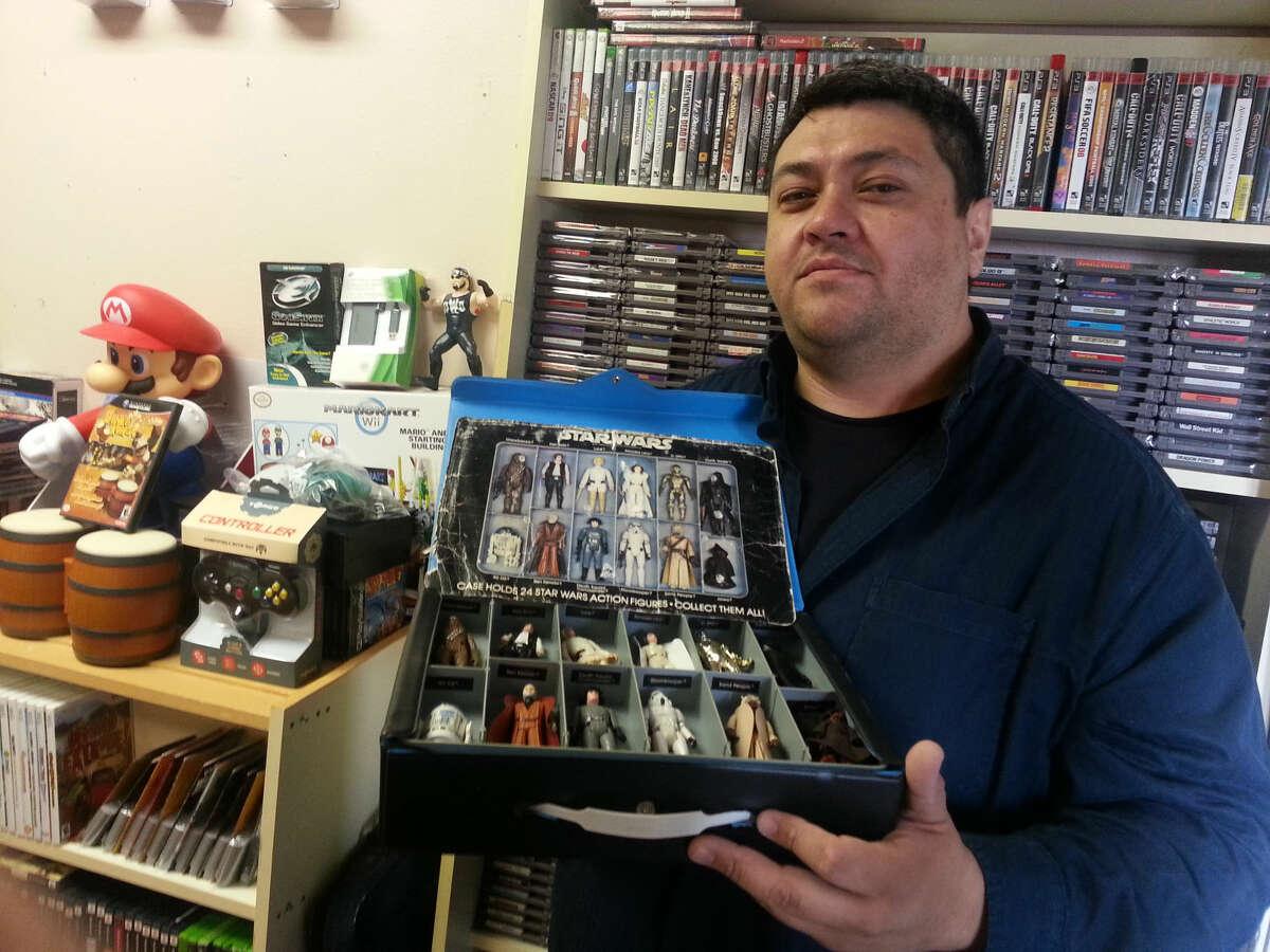Jaekob Mendoza holds collectibles in his Midland store Gamerzville.