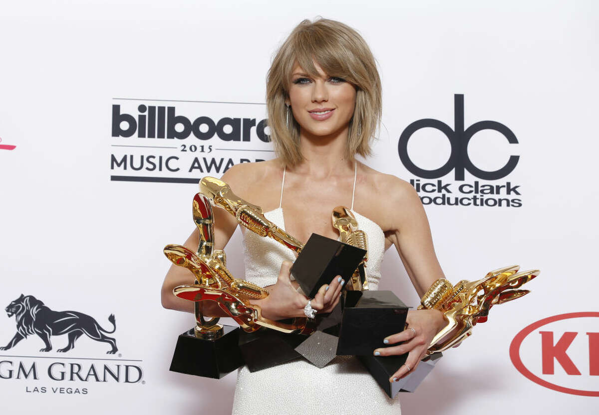"""Taylor Swift poses in the press room with the awards for top Billboard 200 album for """"1989"""", top female artist, chart achievement, top artist, top Billboard 200 artist, top hot 100 artist, top digital song artist, and top streaming song (video) for """"Shake It Off"""" at the Billboard Music Awards at the MGM Grand Garden Arena on Sunday, May 17, 2015, in Las Vegas. (Photo by Eric Jamison/Invision/AP)"""