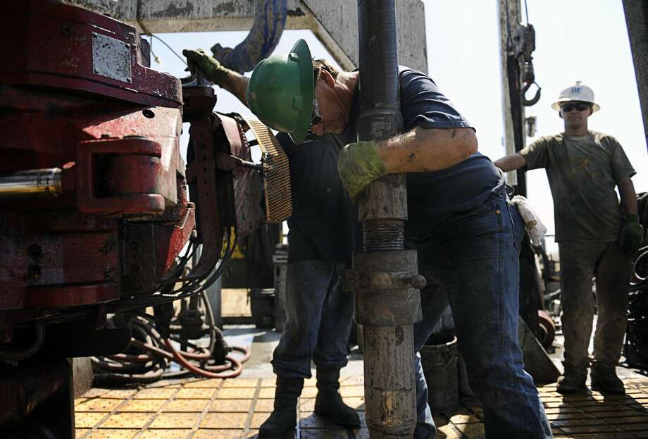 Noble Energy floor hands, left, Jimmy Brown and Justin Fowler work on the company's drill rig in Weld County, Colo. on Thursday, July 29, 2010. New drilling and exploration has slightly increased business in the area since the beginning of the year. Drilling rigs are springing up in areas of Weld County largely bypassed by the natural-gas boom of the past decade. Dying agricultural communities where boarded-up storefronts outnumber open businesses envision a fiscal jolt from oil that could keep the towns' fragile economies afloat. (AP Photo/The Denver Post, Diego James Robles) Photo: Diego James Robles
