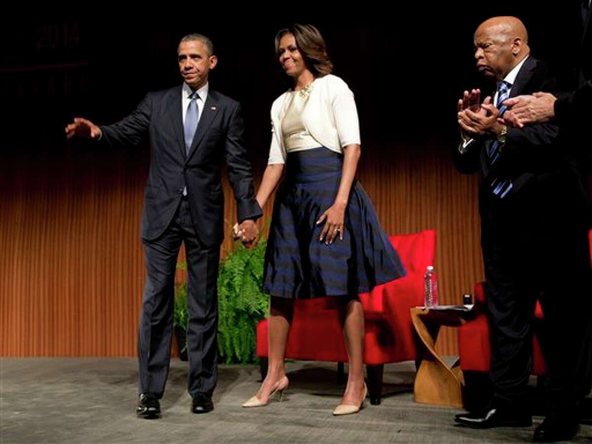 President Barack Obama and first lady Michelle Obama look to the audience as they prepare to leave the stage at the LBJ Presidential Library, Thursday, April 10, 2014, in Austin, Texas, during the Civil Rights Summit to commemorate the 50th anniversary of the signing of the Civil Rights Act. At left is Rep. John Lewis, D-Ga. (AP Photo/Carolyn Kaster)