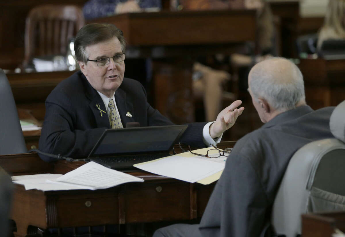 Texas Lt. Gov. Dan Patrick, left, talks with Texas Sen. Kel Seliger, right, R-Amarillo, looks through papers in the Senate Chamber of the Texas Capitol on Tuesday.