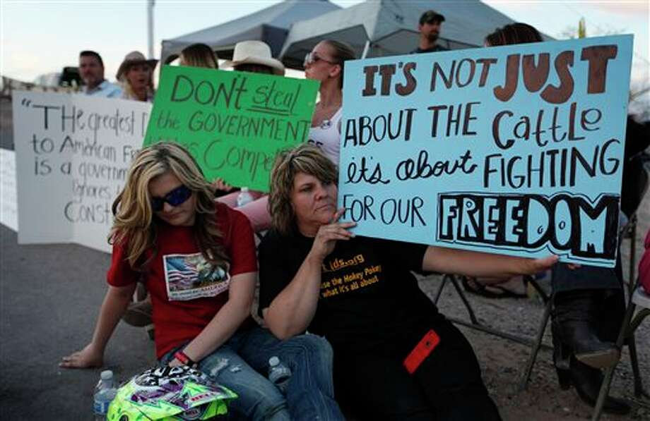 "Krissy Thornton, right, and Burgundy Hall protest with others near Bunkerville, Nev. Wednesday, April 9, 2014. The group is protesting the Bureau of Land Management's roundup of what they call ""trespass cattle"" run by Cliven Bundy in the Gold Butte area 80 miles northeast of Las Vegas. (AP Photo/Las Vegas Review-Journal, John Locher) Photo: John Locher / Las Vegas Review-Journal"