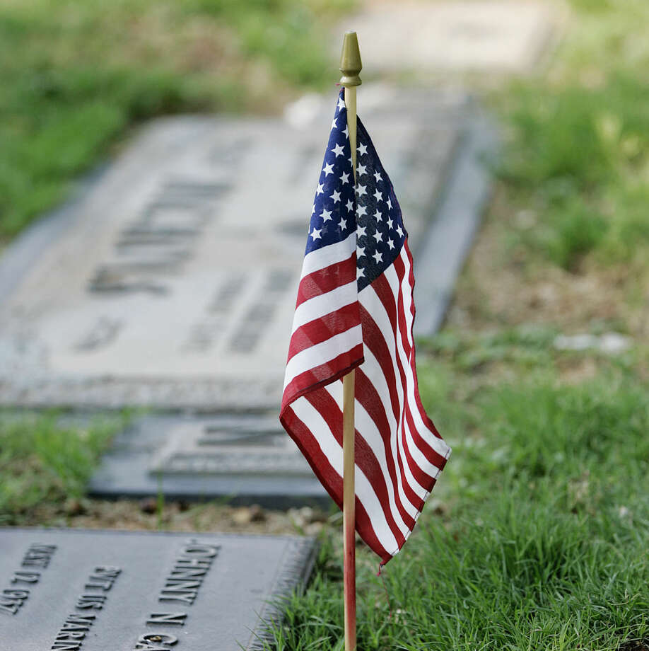 An American flag stands near the headstone of a military veteran at Resthaven Cemetery.