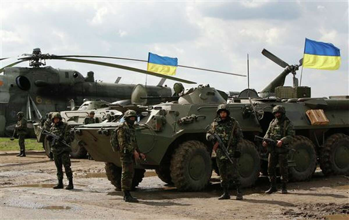 Ukrainian soldiers stand at APCs, with Ukrainian flags in the back, as Ukrainian army troops receive ammunition in a field on the outskirts of Izyum, Eastern Ukraine, Tuesday, April 15, 2014. An Associated Press reporter saw at least 14 armored personnel carriers with Ukrainian flags, one helicopter and military trucks parked 40 kilometers (24 miles) north of the city on Tuesday. (AP Photo/Sergei Grits)