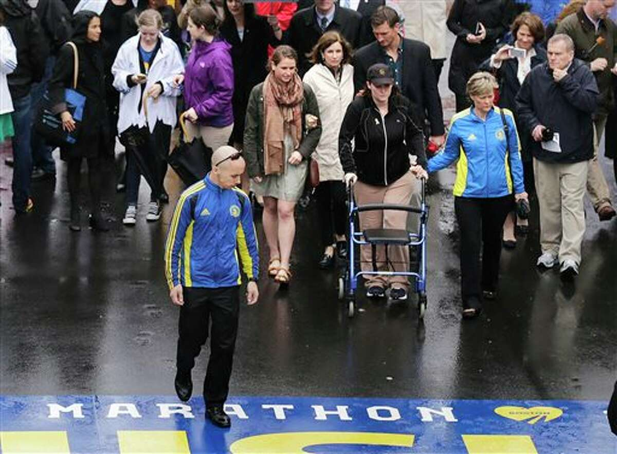 Marathon survivor Erika Brannock, a teacher from Maryland, uses a walker as she prepares to cross the finish line following a tribute in honor of the one year anniversary of the Boston Marathon bombings, Tuesday, April 15, 2014 in Boston. (AP Photo/Charles Krupa)