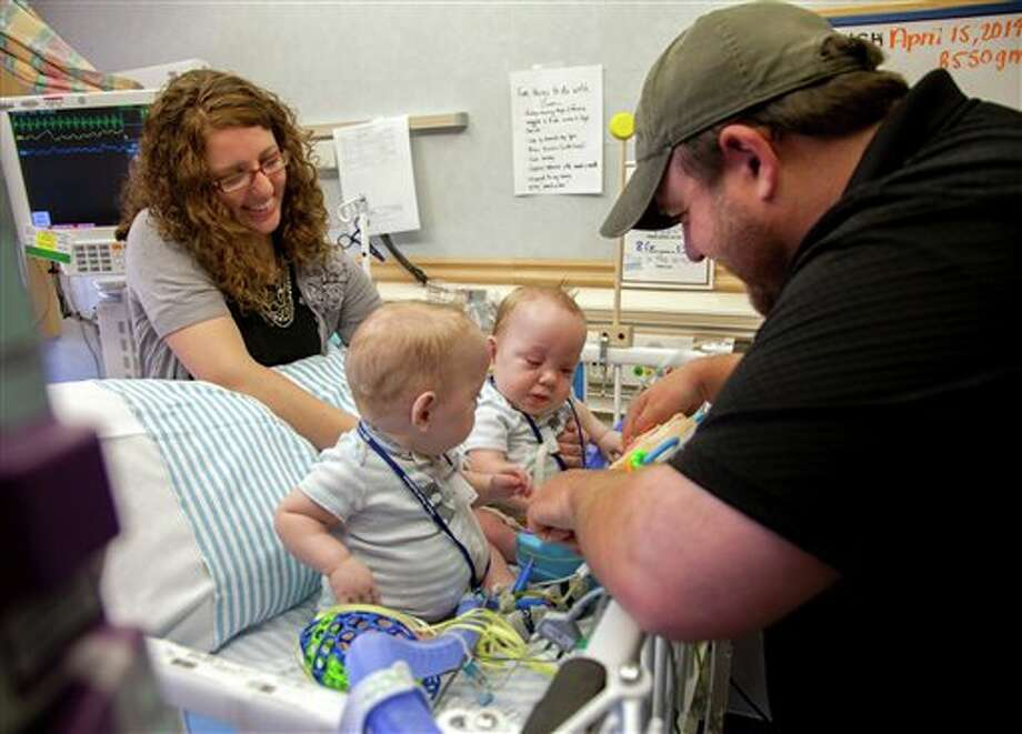 In this Tuesday, April 15, 2014 photo provided by Medical City Children's Hospital in Dallas, Jenni and Dave Ezell visit their twin 9-month-old boys Owen, left, and Emmett, who were born joined at the abdomen. The conjoined twins, separated last summer, were released from the hospital Wednesday and are expected to spend the next three to four weeks in a local inpatient rehabilitation center before being able to go home. (AP Photo/Medical City Children's Hospital) Photo: HOEP / Medical City Children's Hospital