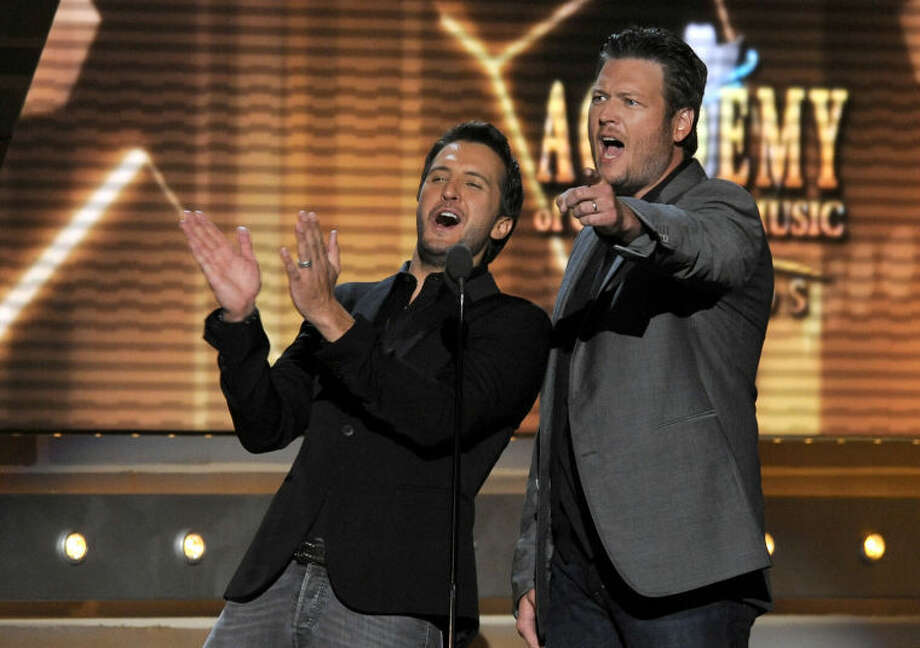 FILE - In this April 7, 2013 file photo, Luke Bryan, left, and Blake Shelton speak on stage at the 48th Annual Academy of Country Music Awards at the MGM Grand Garden Arena in Las Vegas. The 2014 Academy of Country Music Awards in Las Vegas will air live Sunday night, April 6, 2014, from 8-11 p.m. EDT on CBS. Several awards, including top honor entertainer of the year, will be announced during the broadcast, to be hosted by Blake Shelton and Luke Bryan. Shelton, Bryan, George Strait, Miranda Lambert, Jason Aldean, Keith Urban, Tim McGraw, Shakira and Stevie Nicks are scheduled to perform. (Photo by Chris Pizzello/Invision/AP, File) Photo: Chris Pizzello