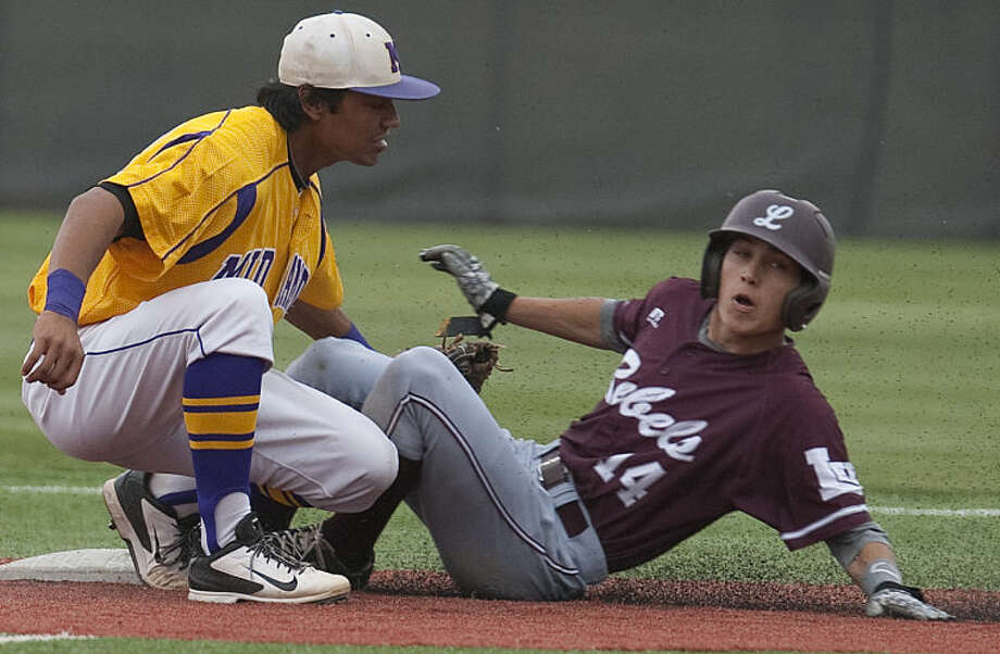Lee High's Garrett Chalker safely slides into second under the tag of Midland High's Gilbert Sanchez April 11 at Christensen Stadium. Tim Fischer\Reporter-Telegram Photo: Tim Fischer