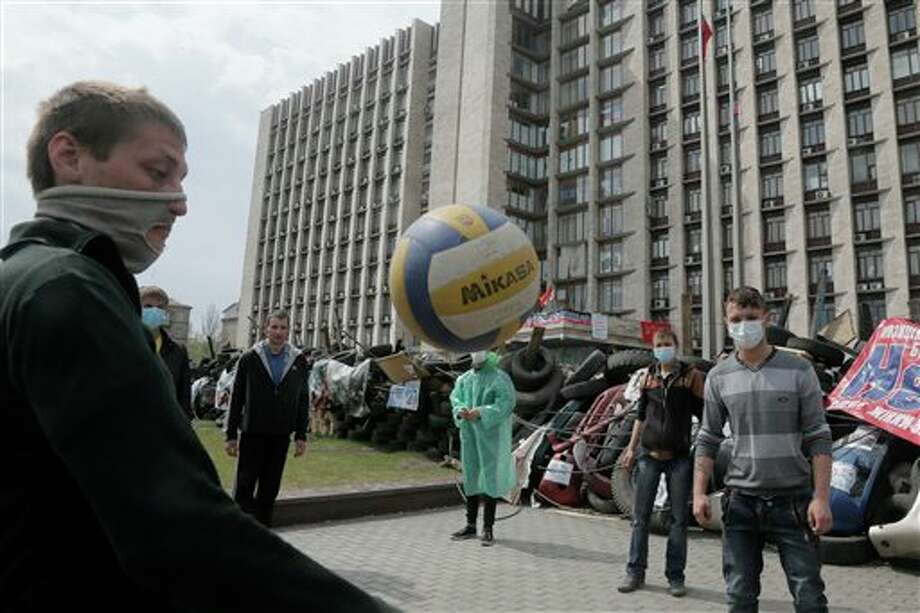 Masked pro-Russian activists play with a ball as they guard a barricade at the regional administration building that they had seized earlier in Donetsk, Ukraine, Saturday, April 19, 2014. Pro-Russian insurgents defiantly refused Friday to surrender their weapons or give up government buildings in eastern Ukraine, despite a diplomatic accord reached in Geneva and overtures from the government in Kiev. (AP Photo/Efrem Lukatsky) Photo: Efrem Lukatsky / AP