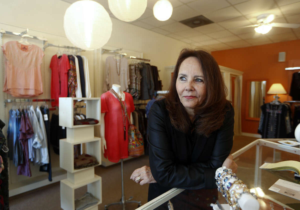 In this April 24, 2015 photo, Razzle Dazzle dress shop owner Carol Avendano poses at her store in the Buckhead section of Atlanta. Razzle Dazzle's revenue is down 65 percent from 2007. Avendano sees customers think carefully before spending. (AP Photo/John Bazemore)