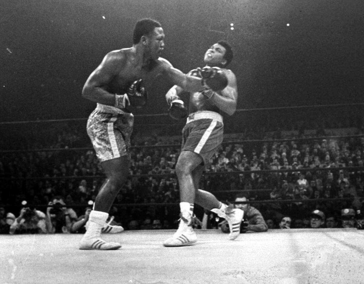 FILE - In this March 8, 1971, file photo, boxer Joe Frazier, left, hits Muhammad Ali during the 15th round of their heavyweight title fight at New York's Madison Square Garden. Can the Mayweather-Pacquiao fight ever live up to its hype? Comparing this fight to other great matches in history that actually lived up to their hype, and to several that were disappointments. (AP Photo/File)