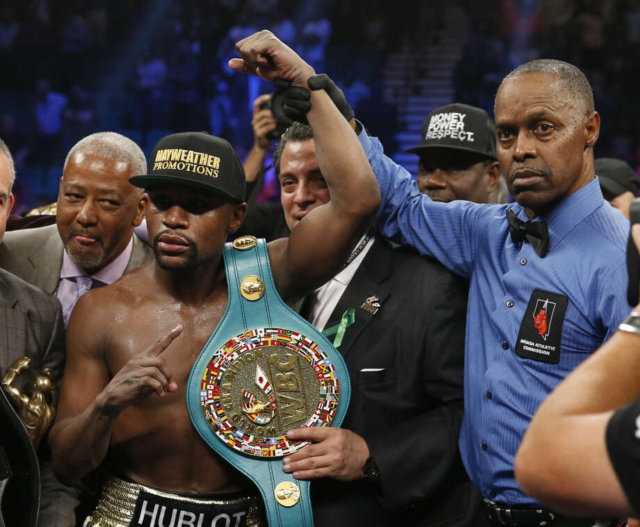 Floyd Mayweather Jr., left, holds up the title belt next to referee Kenny Bayless after his win against Manny Pacquiao, from the Philippines, in their welterweight title fight on Saturday, May 2, 2015 in Las Vegas. (AP Photo/John Locher) Photo: John Locher