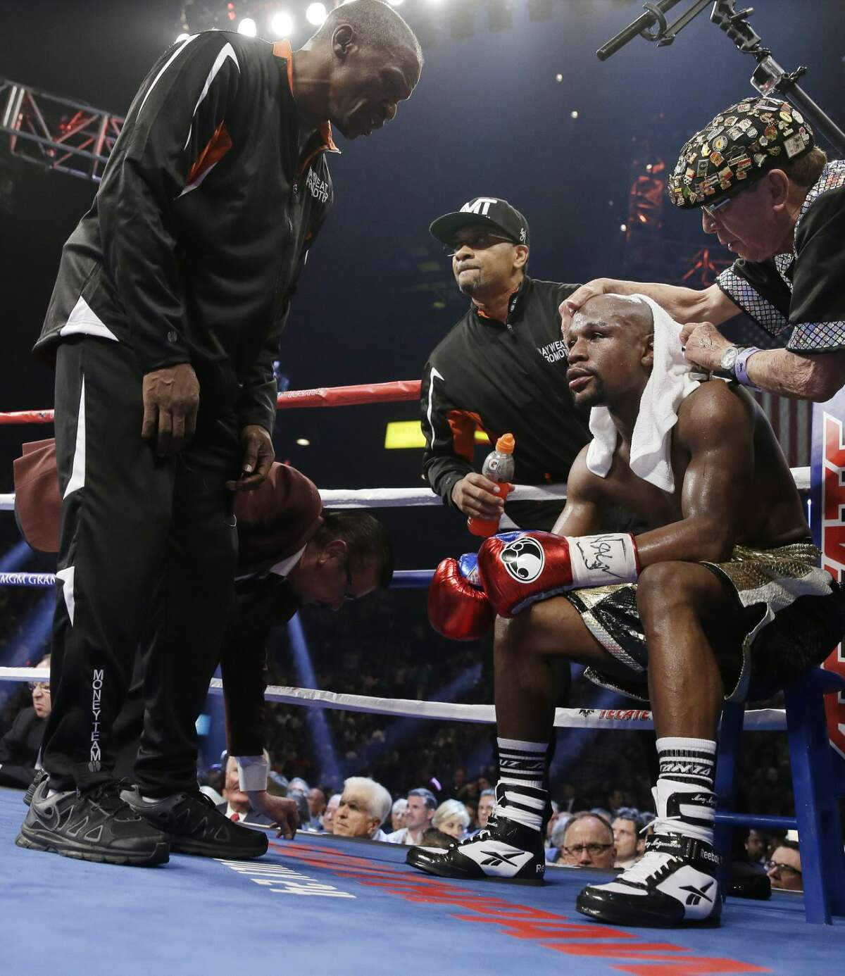 Floyd Mayweather Jr., right, sits in his corner with his father, head trainer Floyd Mayweather Sr., left, during his welterweight title fight against Manny Pacquiao on Saturday, May 2, 2015 in Las Vegas. (AP Photo/Isaac Brekken)